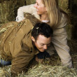 Couple playing in hay. — Stok Fotoğraf #9226252