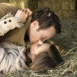 Kissing couple in hay. - Stock Photo