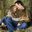 Snuggling couple in hay. — Foto de Stock