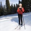 Female Snow Skiier Leaning on Poles and Smiling - Stock Photo
