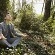 Young Businessman Sitting in Meditation - Stock Photo