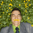 Smiling Businessman in Flower Patch - Foto Stock