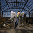 Businessman Wearing Angel Wings - Stock Photo