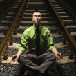 Businessman Meditating on Railroad Tracks. - Стоковая фотография