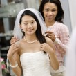 Friend helping bride. - Stock Photo
