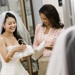 Woman helping bride with handbags. - Stock Photo