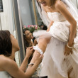 Foto Stock: Bridesmaid placing garter.
