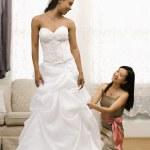 Bridesmaid adjusting bride's dress. — Stock Photo