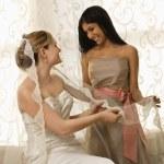 Bridesmaid holding bride's veil. — Stock Photo