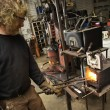 Metalsmith heating metal in forge. - Stock Photo