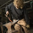 Metalsmith shaping metal. - Stock Photo