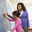 Teacher and Student at Blackboard - Stock Photo