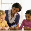 Teacher Helping Students With Schoolwork - Stock Photo