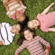 Stock Photo: Children Lying in Clover With Heads Together