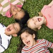 Children Lying in Clover Screaming With Heads Together - Stock Photo