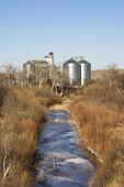 Storage silos by creek. — Stock Photo