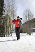 Adolescente carregando equipamento de esqui. — Fotografia Stock