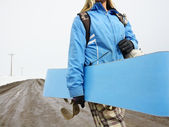 Woman carrying snowboard. — Stock Photo