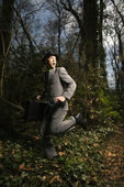 Young Businessman Running In Woods — Stock Photo