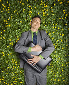 Businessman Lying in Flower Patch — Stock Photo