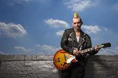 Punk holding guitar. — Stock Photo