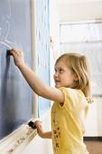 Girl Writing on Blackboard — Stock Photo
