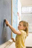 Girl Erasing Writing on Blackboard — Stock Photo