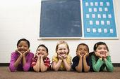 Studenten liggend op de vloer in klas. — Stockfoto