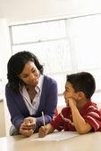 Učitelka pomáhá chlapec s školní — Stock fotografie