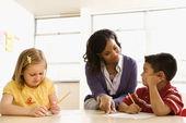 учитель помогает студентам в школе — Стоковое фото
