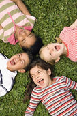 Children Lying in Clover Screaming With Heads Together — Stock Photo