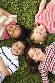 Bambini sdraiato nel trifoglio con teste insieme — Foto Stock