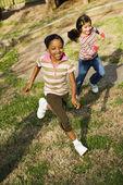 Unga tjejer kör på gräs — Stockfoto