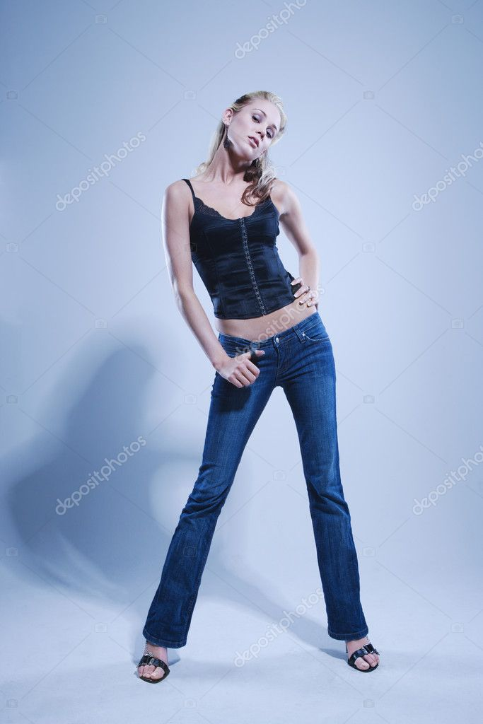 Blue toned full length studio portrait of pretty blonde Caucasian young woman. — Stock Photo #9221677