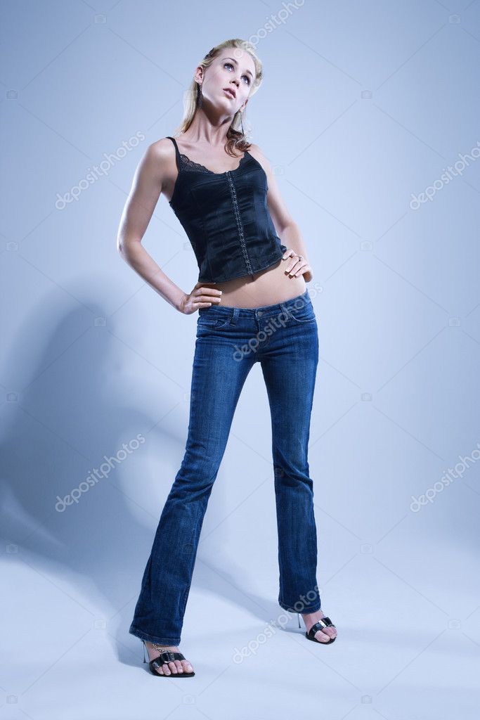 Blue toned full length studio portrait of pretty blonde Caucasian young woman.  Stock Photo #9221681