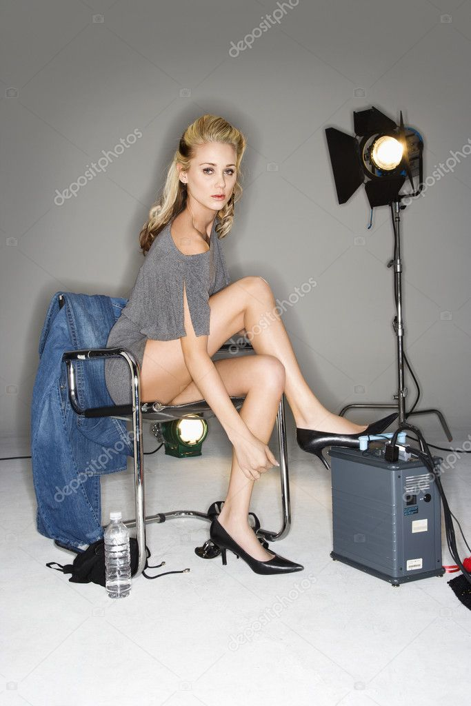 Pretty young Caucasian blonde woman sitting with studio lights. — Stock Photo #9221724
