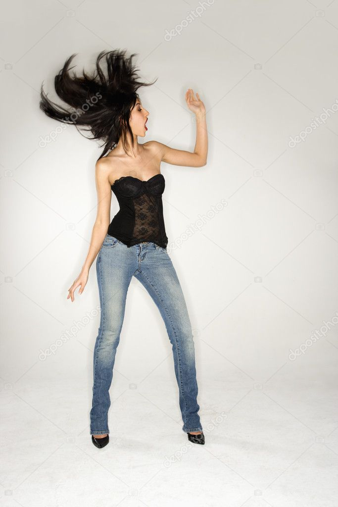 Full length portrait of pretty young woman flinging long, black hair. — Photo #9221797