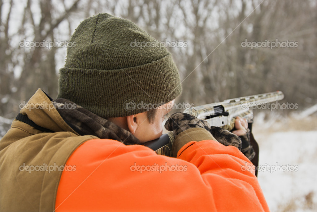 Caucasian male aiming shotgun out towards woods. — Stock Photo #9223003
