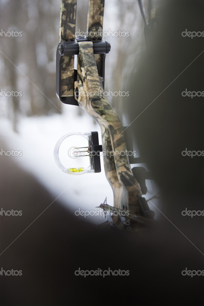 Camouflage bow and arrow with blurred foreground. — Stock Photo #9223014