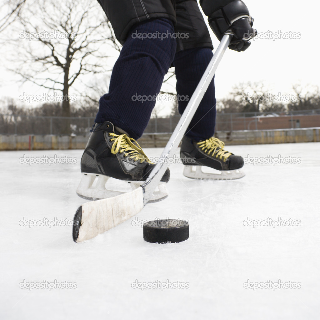 Boy in ice hockey uniform skating on ice rink moving puck.  Stock Photo #9224628