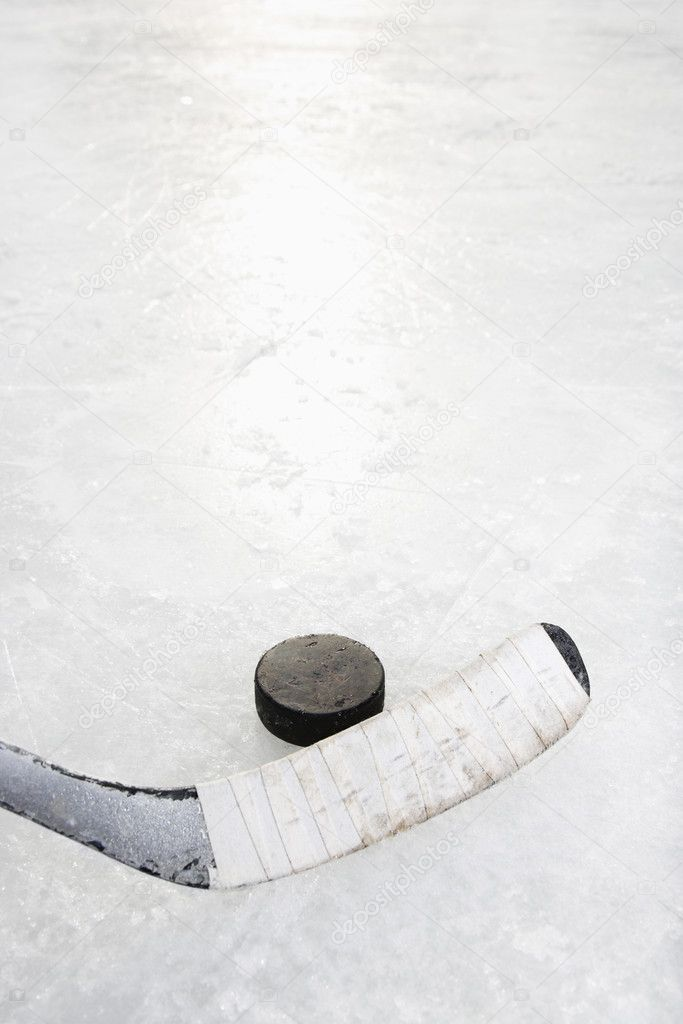 Close up of ice hockey stick on ice rink in position to hit hockey puck. — Stock Photo #9224653