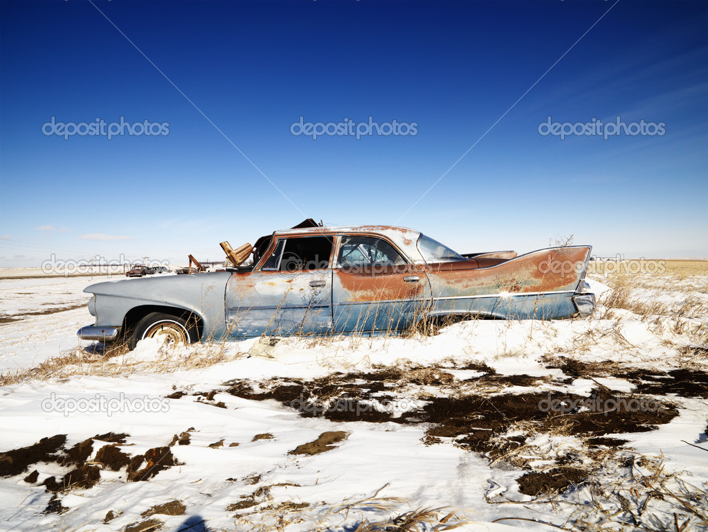 Classic rusted car in snowy junkyard. — Stock Photo #9225085