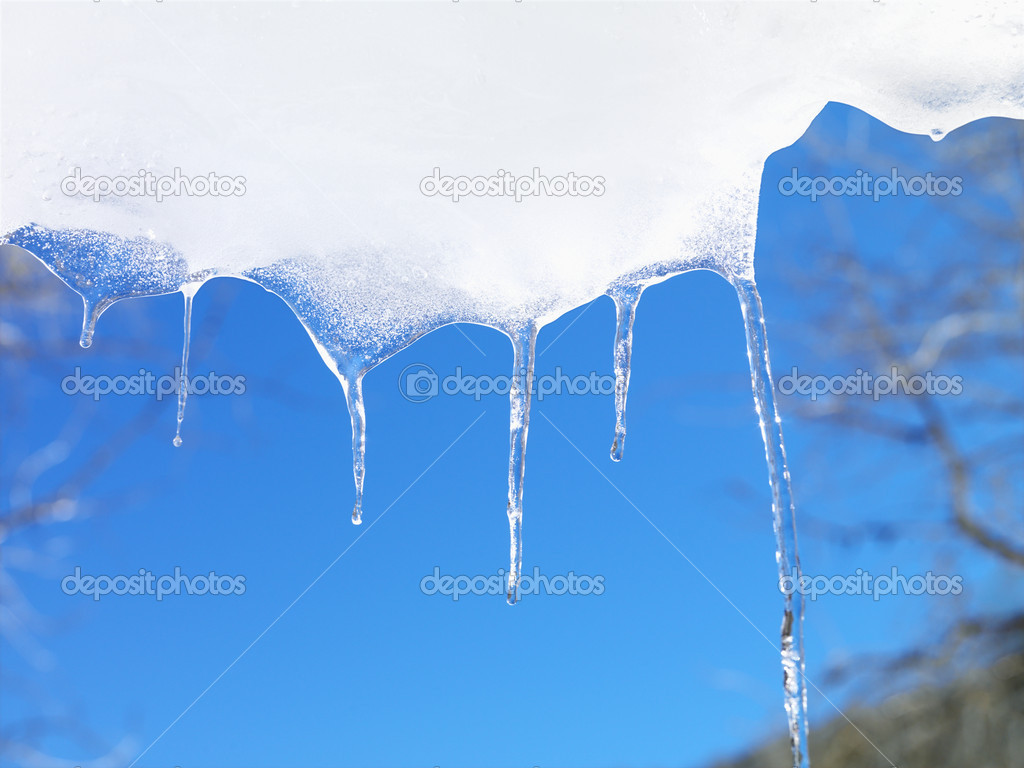 Icicles hanging down from snow and ice with a blue sky in the background. Horizontal shot. — Stock Photo #9225917