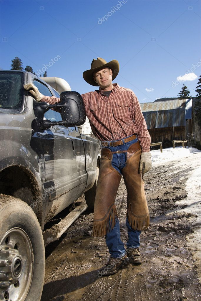 Man wearing a cowboy hat and leaning against a pickup truck. Vertical shot  Stock Photo #9226046