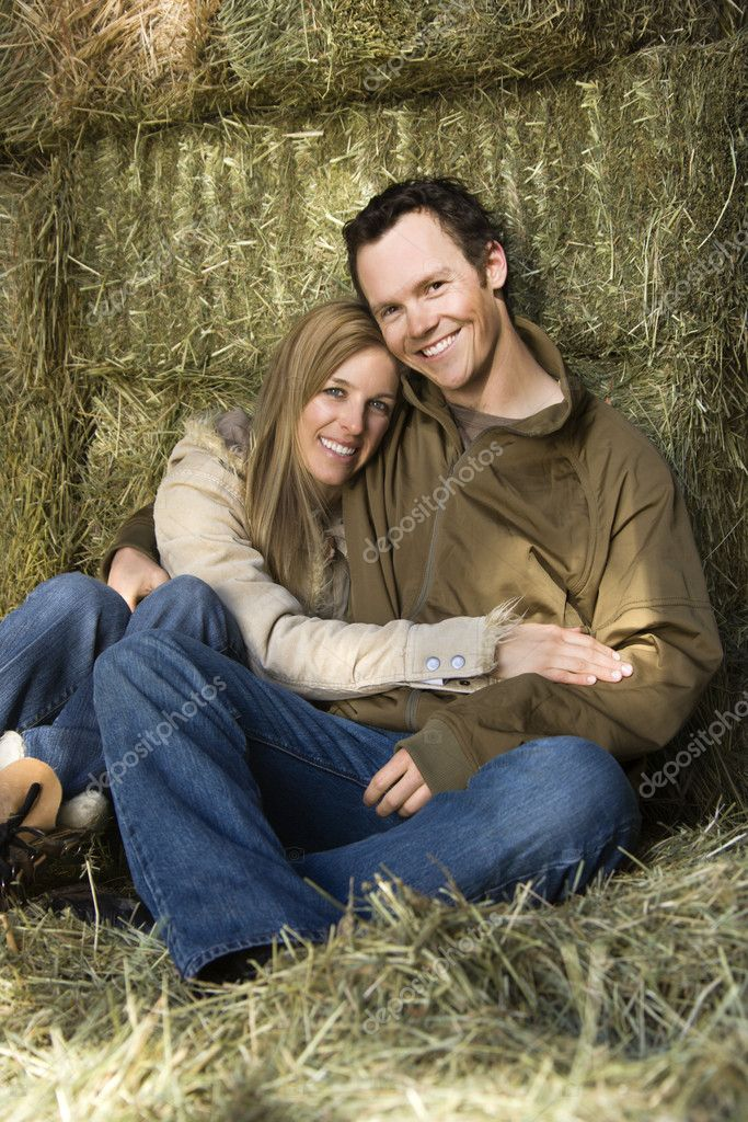 Young adult Caucasian couple sitting on hay hugging and smiling at viewer. — Stock Photo #9226263