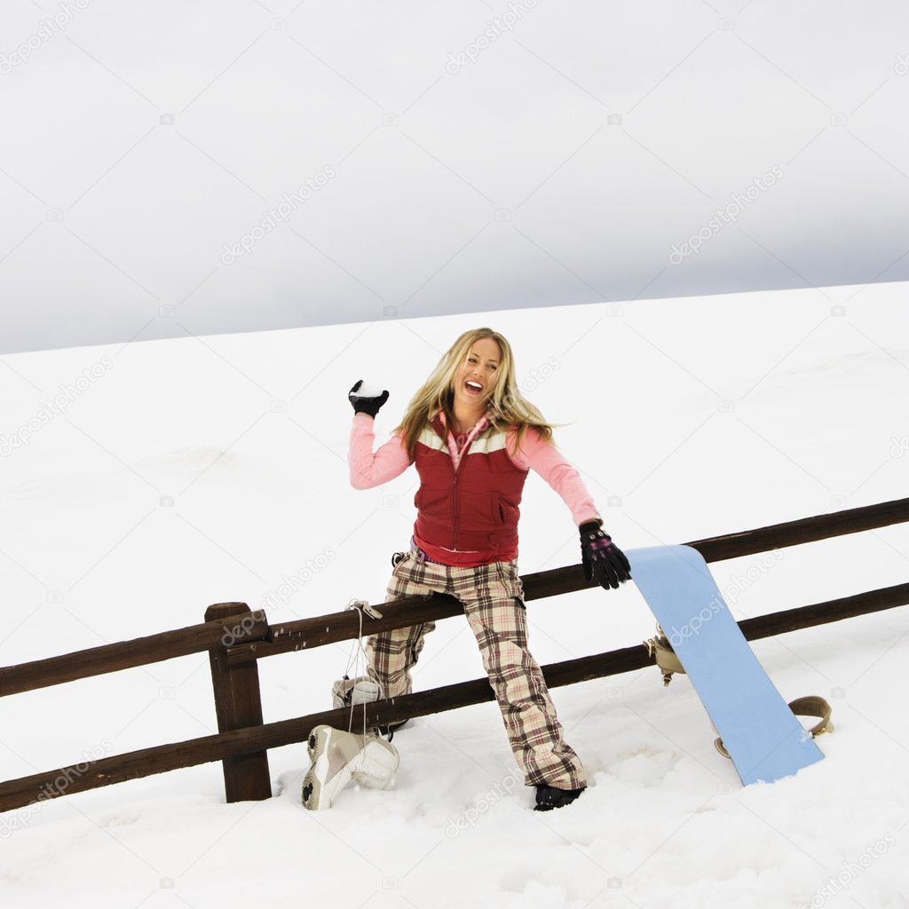Young woman in winter clothes by fence in snowy field smiling while ready to throw snowball.  Stock Photo #9226732