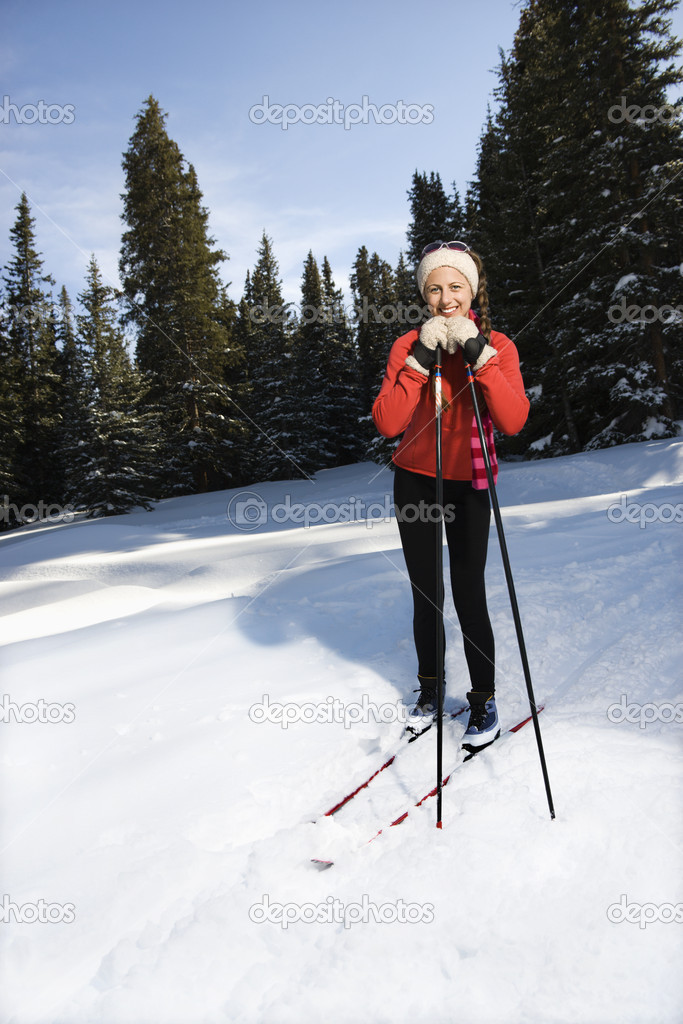 Female snow skiier smiling, standing in the snow leaning on ski poles.  Vertically framed shot. — Stock Photo #9226871