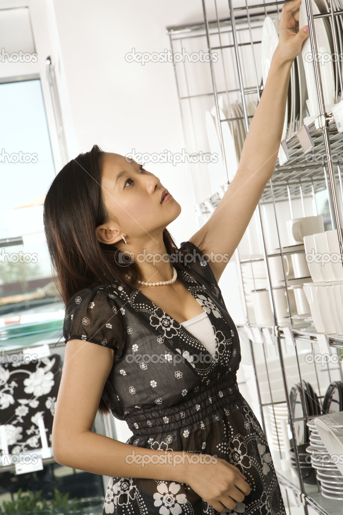 Asian female shopping for dishes and glasses in retail store. — Stock Photo #9227283