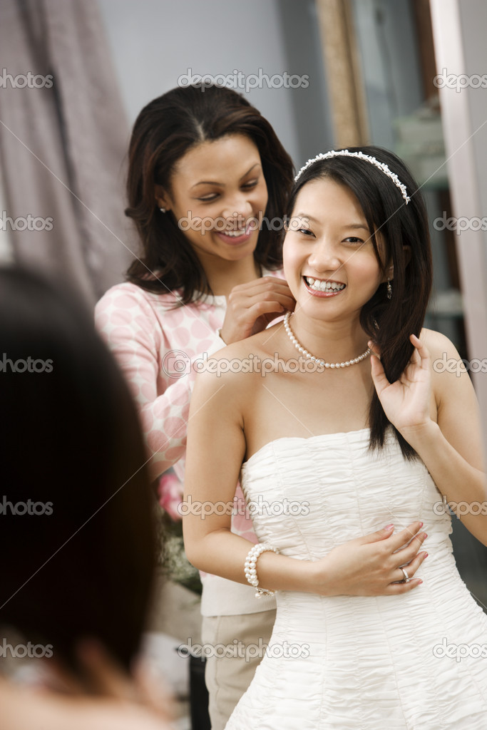 African-American friend helping place necklace on Asian bride.  Foto Stock #9227458