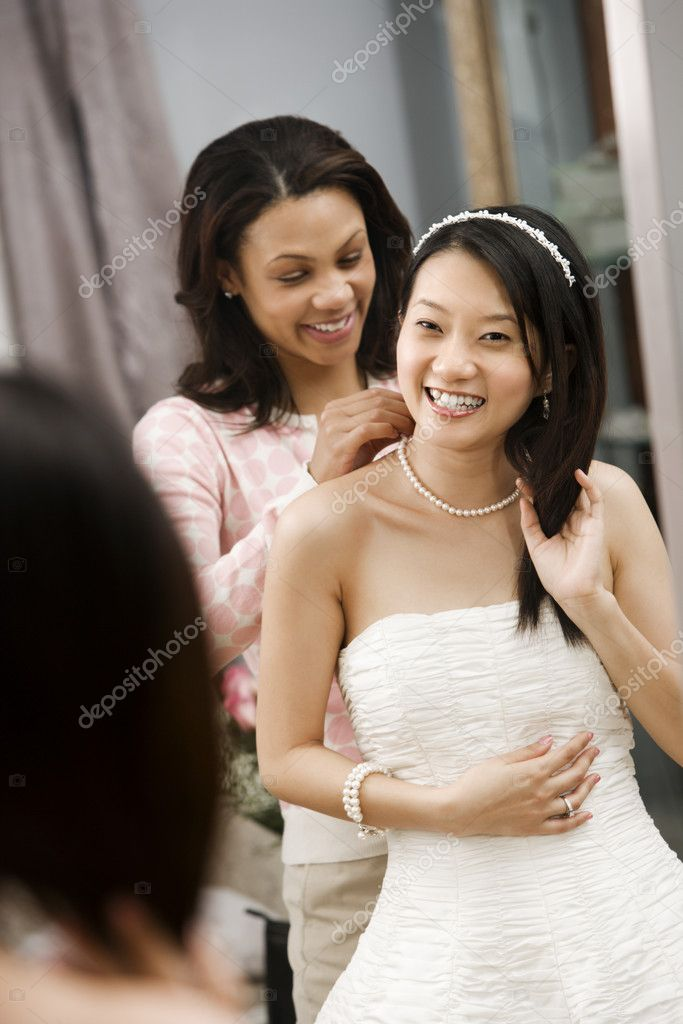 African-American friend helping place necklace on Asian bride. — Photo #9227458